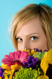 Woman with Flowers. Close-up portrait of a beautiful, blue-eyed, blond woman with colorful flowers on the foreground Royalty Free Stock Image