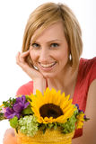 Woman with flowers. Portrait of a beautiful blond woman with colorful flowers in the foreground. Isolated on a white background Stock Photo