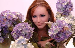 Woman and flowers. A  beautiful red-haired young woman looking through lavender hydrangeas Royalty Free Stock Images