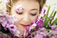 Woman with flowers. Woman enjoying her flowers Royalty Free Stock Image