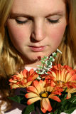 Woman with flowers. Young woman holding flowers and looking at them Stock Photography