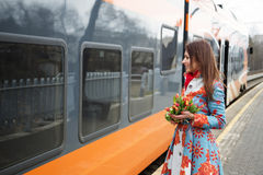 Woman with flowers adopt finaly come train Royalty Free Stock Photo
