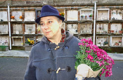 Woman with flowers at the cemetery Royalty Free Stock Photography