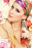 Woman in flowers. Fashion woman in silk shawl surrounded by colorful flowers Stock Image