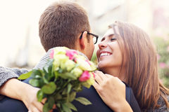 Woman with flowers giving hug to her man Stock Image