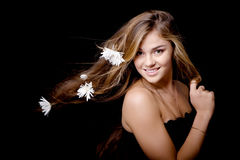 Woman with flowers in hair. Beautiful attractive young smiling girl with white flowers in her hair blowed by wind ob black royalty free stock photography