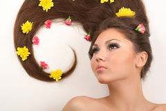 Woman with flowers in hair. Attractive young woman with beautiful healthy hair lying on white background covered with flowers Royalty Free Stock Images
