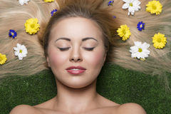 Woman with flowers in hair. Lovely girl with relaxed expression and perfect skin posing in close-up beauty portrait lying on garden with some colourful flowers Stock Photo