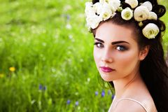 Woman with flowers in hair sitting on blooming meadow Stock Images
