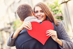 Woman with flowers and heart giving hug to her man. Picture showing happy couple hugging with flowers and heart in the city Stock Images