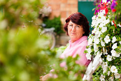 Woman with flowers in her garden Royalty Free Stock Photography