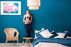 Woman with flowers at home. Beautiful young woman holding flowers standing in the cozy bedroom on the blue wall background at home royalty free stock image