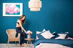 Woman with flowers at home. Young woman decorating bedroom with beautiful flowers at home stock photography