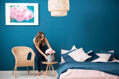 Woman with flowers at home. Young woman decorating bedroom with beautiful flowers at home stock image