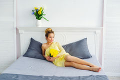 Woman with flowers posing on the bed Royalty Free Stock Image