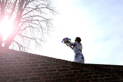 Woman with flowers reaching for the tree and the sun Royalty Free Stock Photography
