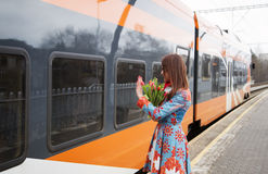Woman with flowers salute to train passanger Stock Images