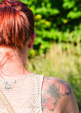Woman with flowers tattoo. Young woman with flowers tattoo on her right shoulder blade. Image royalty free stock images