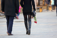 Woman with flowers tulips in his hand, walking next to the man Royalty Free Stock Images