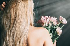 Woman flowers by window, bare shoulders, back view stock photography