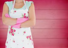 Woman in flowery apron with arms folded against blurry pink wood panel Royalty Free Stock Photos