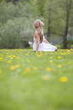Woman in flowery field. Young blond haired woman relaxing on green field in park or countryside with yellow flowers, summer scene Stock Photography