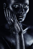 Woman in flowing black paint touching face Stock Image