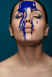 Woman with flowing blue paint Stock Photography