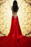 Woman in Flowing Satin Dress. The back of a beautiful woman goddess in a bright red satin flowing dress. She is standing in front of a golden background Royalty Free Stock Photography