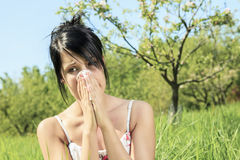 Woman with a flu or an allergy. A Woman with a flu or an allergy sitting on the long grass Stock Photo