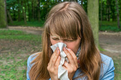 Woman with flu or allergy symptoms in park Royalty Free Stock Photo