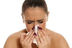 Woman with a flu. Beautiful woman with a flu sniffling in a napkin Stock Image