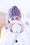 Woman with flu blowing nose at home Stock Photo
