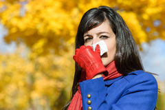 Woman with flu and cold outdoors. Woman with flu blowing her nose with a kleenex on a cold autumn day Royalty Free Stock Photography