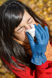 Woman with flu and cold sneezing outdoors. Woman with flu sneezing and blowing her nose with a kleenex on a cold autumn day Royalty Free Stock Photos