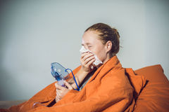 Woman with flu or cold symptoms making inhalation with nebulizer Royalty Free Stock Images