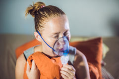 Woman with flu or cold symptoms making inhalation with nebulizer Royalty Free Stock Photos