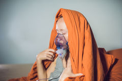 Woman with flu or cold symptoms making inhalation with nebulizer Royalty Free Stock Image