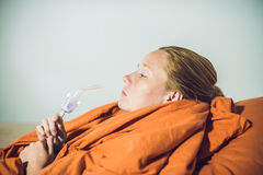 Woman with flu or cold symptoms making inhalation with nebulizer Stock Image