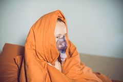 Woman with flu or cold symptoms making inhalation with nebulizer Royalty Free Stock Photography