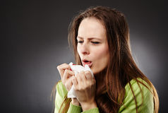 Woman with flu coughing. Young woman with flu coughing, holding a white tissue Stock Image