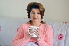 Woman with flu symptoms holding a cup in  hand Royalty Free Stock Image
