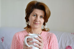 Woman with flu symptoms holding a cup in  hand Stock Photo