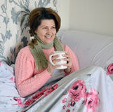 Woman with flu symptoms holding a cup in  hand Royalty Free Stock Photos