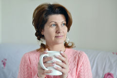 Woman with flu symptoms holding a cup in  hand Royalty Free Stock Photography
