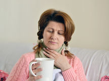 Woman with flu symptoms holding a cup in  hand Stock Photography