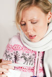 Woman with flu taking her temperature Stock Photography