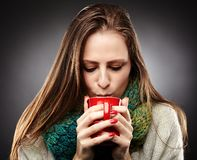 Woman with flu wrapped up in a scarf and drinking hot tea. Closeup of  a woman with flu wrapped up in a scarf and drinking hot tea over gray background Stock Photo