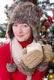 Woman in fluffy hat and mitten under Christmas tree with cup. Smiling woman in fluffy hat and mitten under Christmas tree with cup Royalty Free Stock Photography