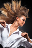Woman with fluttering hair. On dark background Stock Image